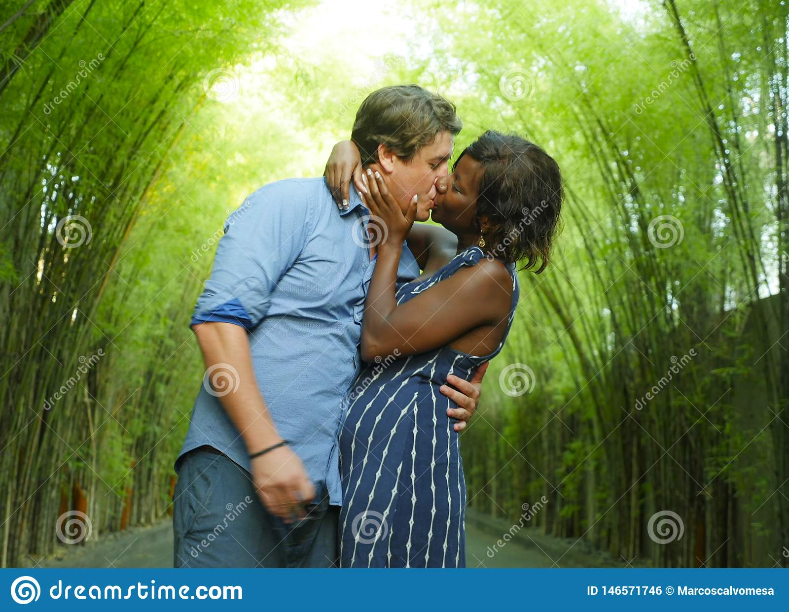 Happy mixed ethnicity couple kissing outdoors with attractive black African American woman and handsome Caucasian boyfriend or