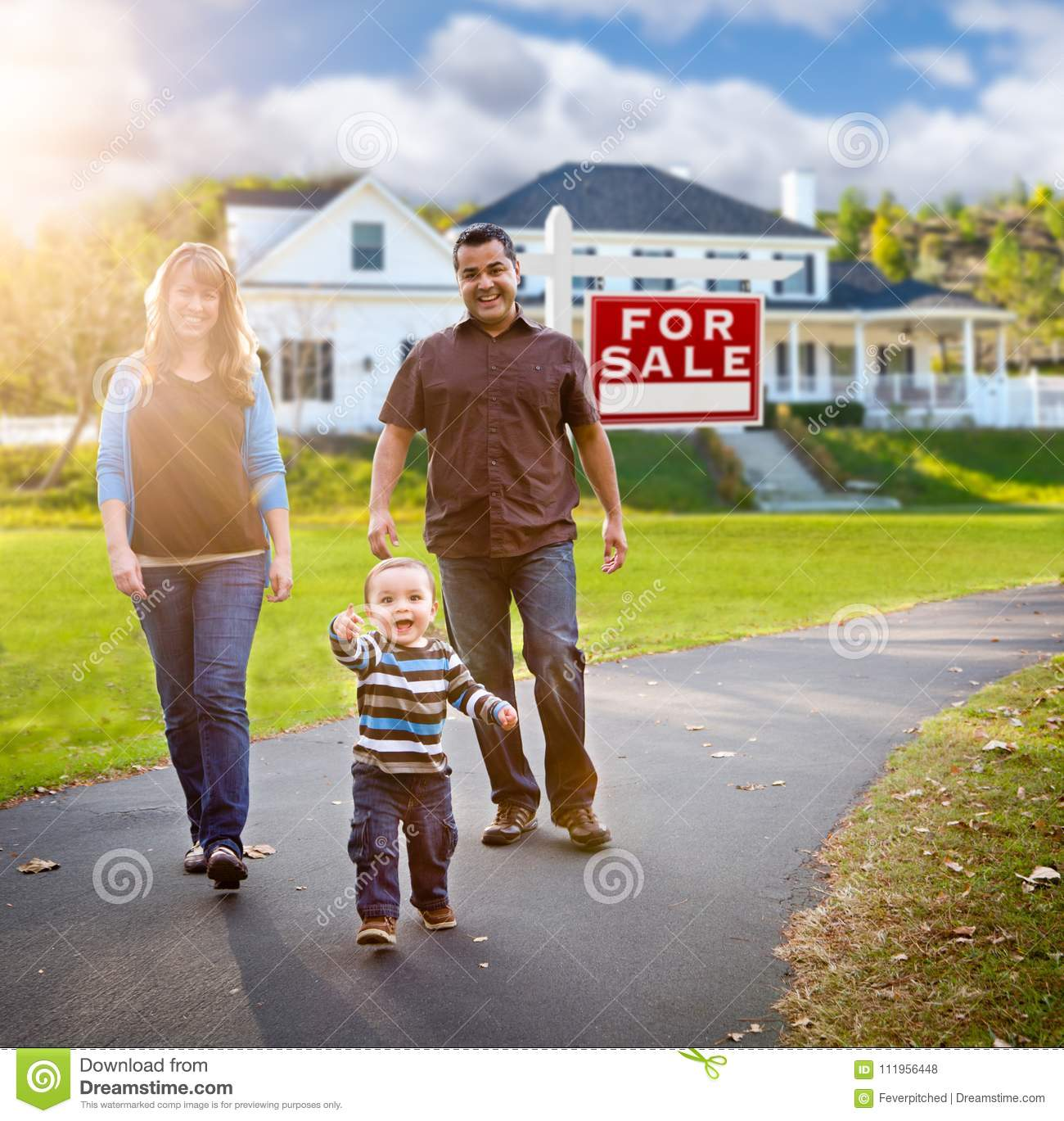 Happy Mixed Race Family in Front of Home and For Sale Sign