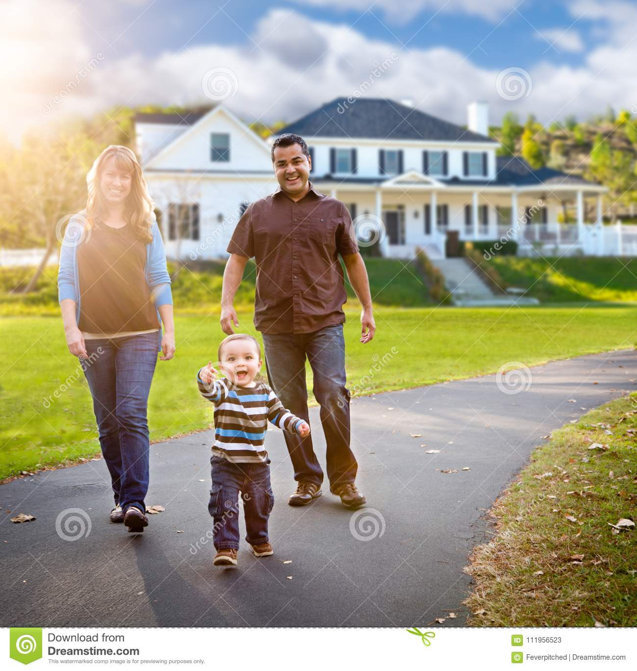 Happy Mixed Race Family Walking in Front of Beautiful Custom Home