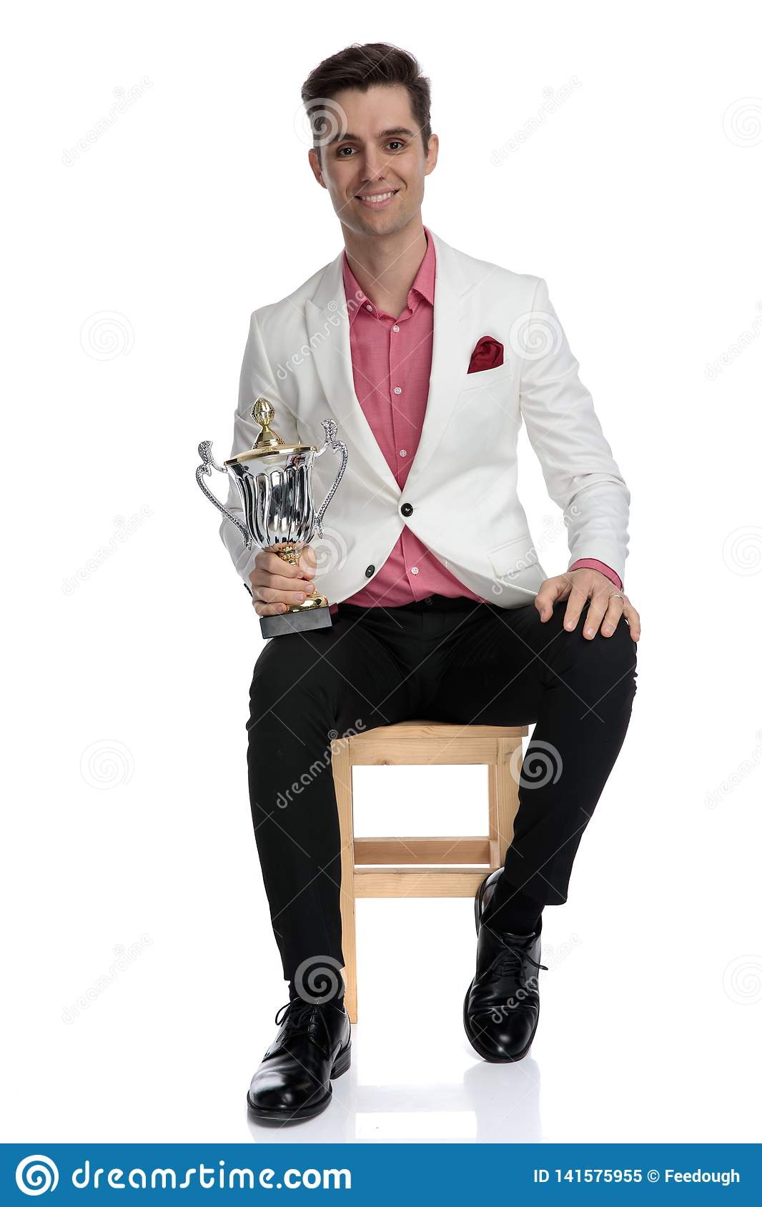Happy modern businessman sitting with his trophy cup
