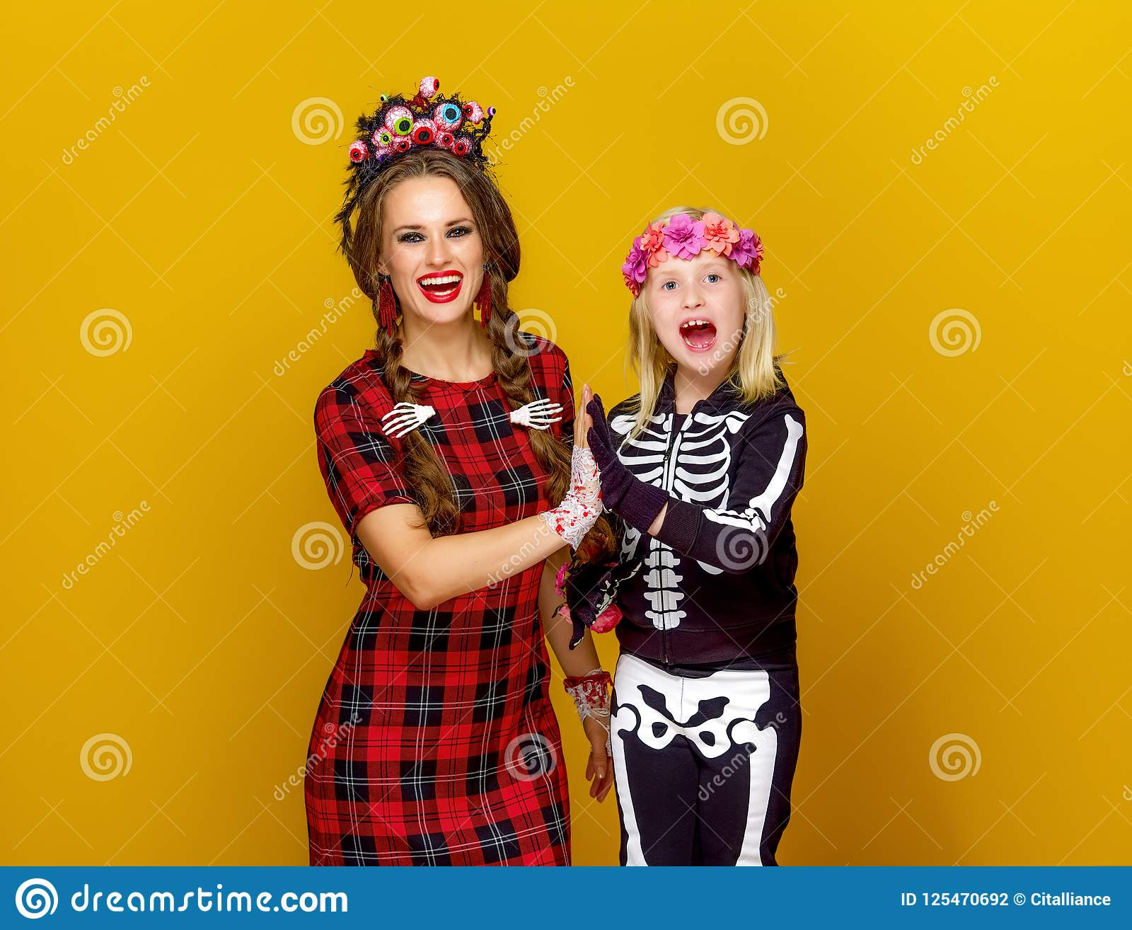 Happy modern mother and child in halloween costume high five