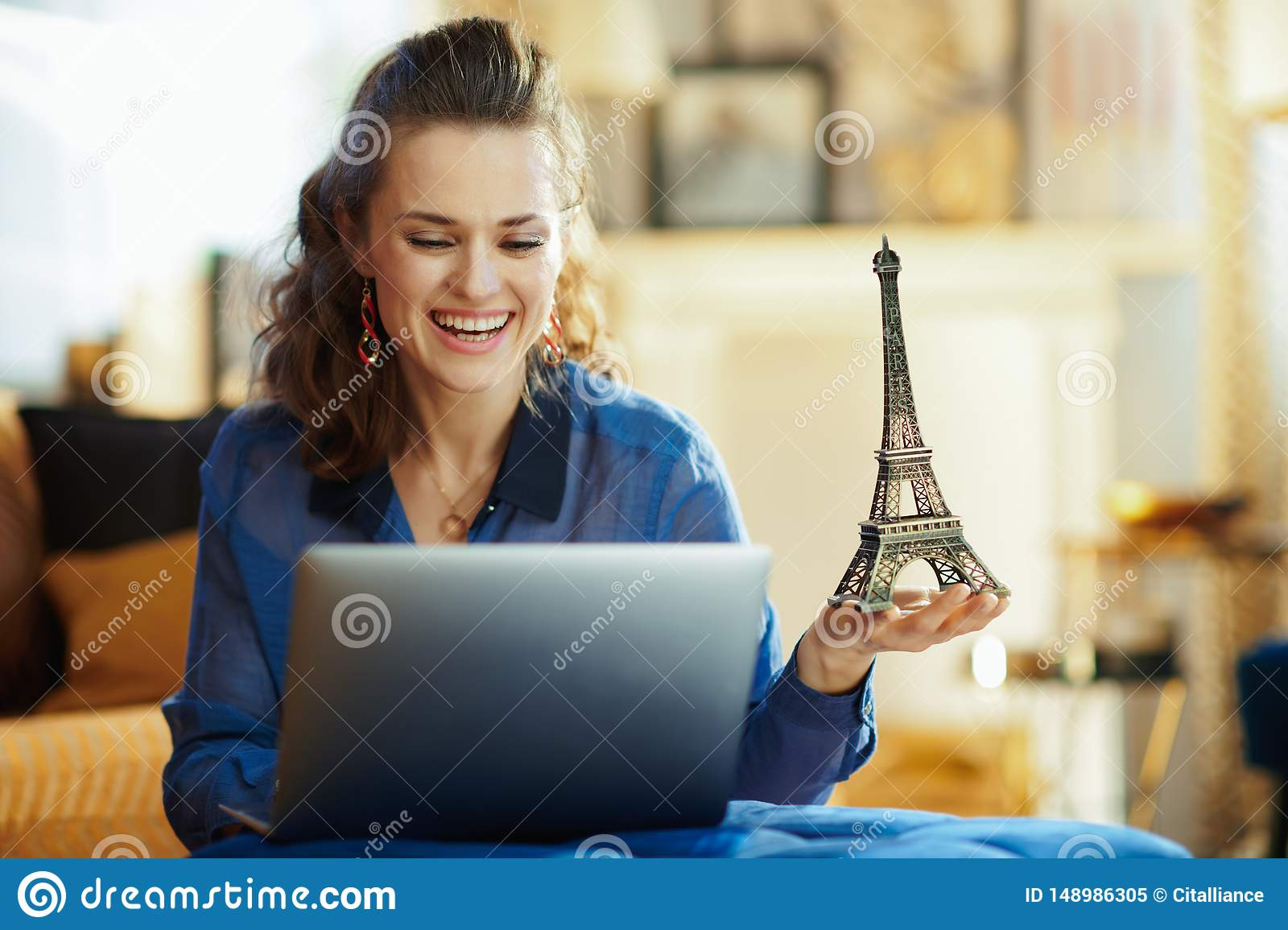 Happy modern woman with souvenir of eiffel tower using laptop