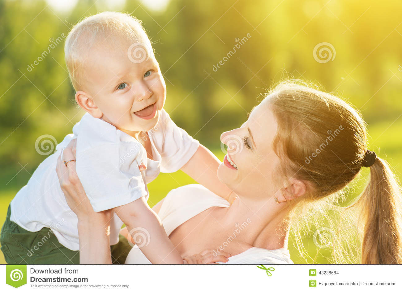 Happy Mom and baby son in summer nature