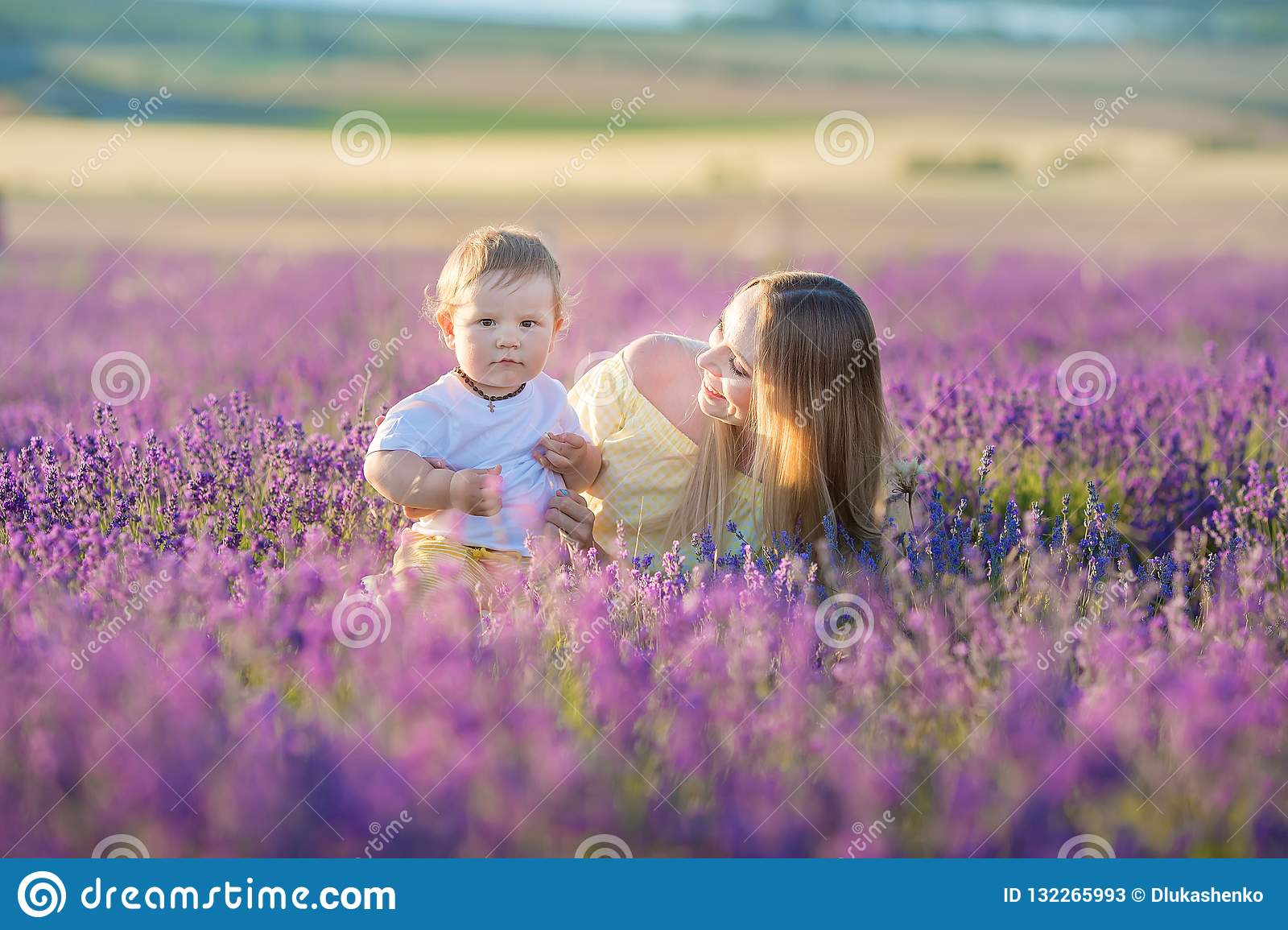 Happy mom with cute son on lavender background. Beautiful woman and boy in meadow field. Lavender landscape with lady and kid