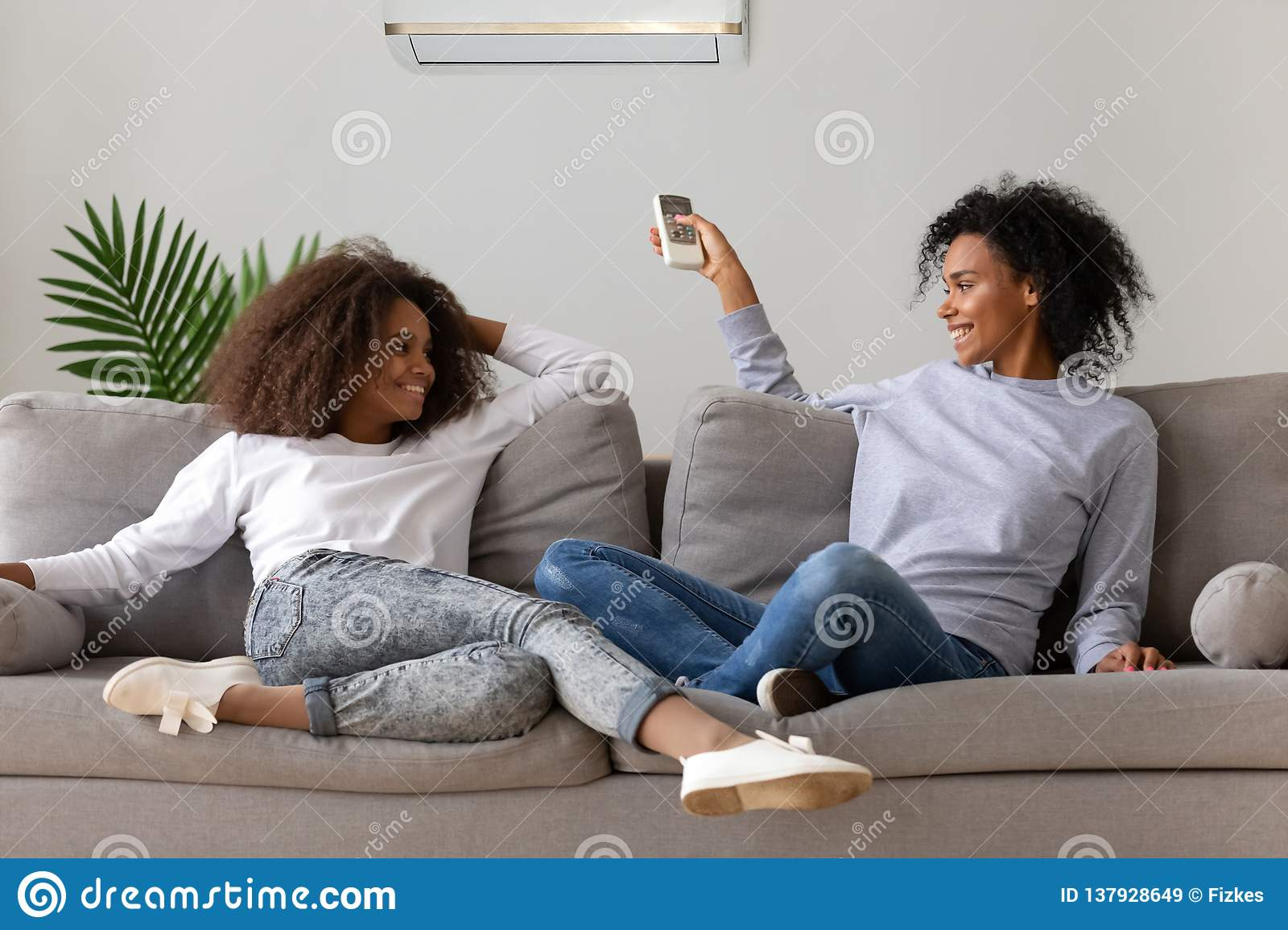 Happy mom and daughter relaxing on couch under air conditioner