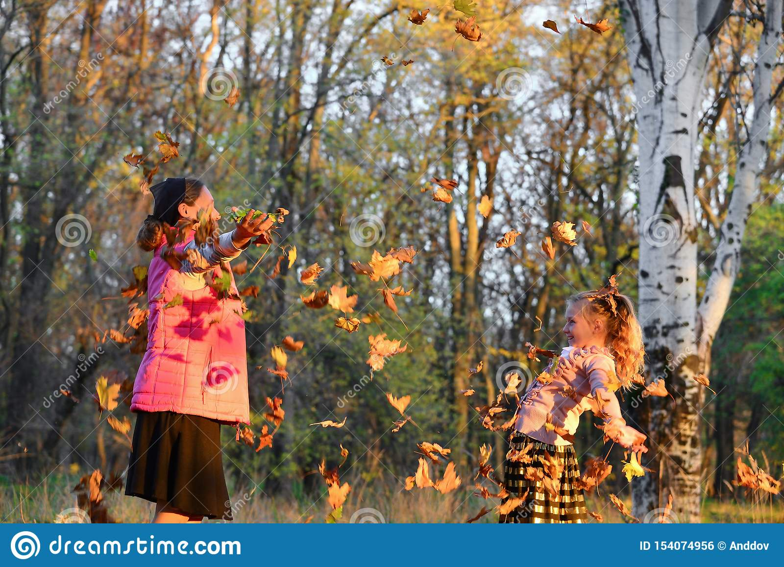 Happy mom and daughter throw autumn leaves up in the park, joyful family