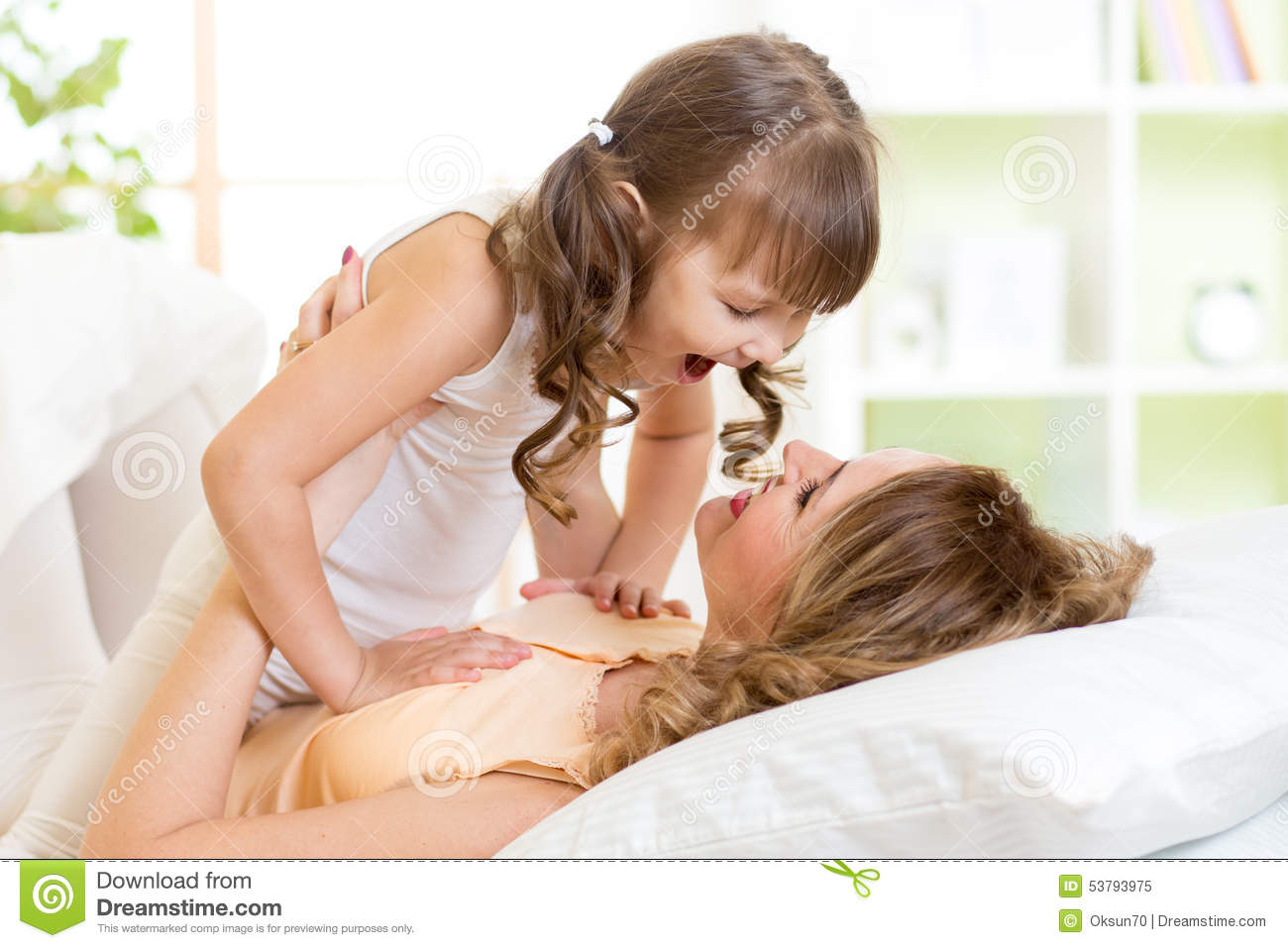 Happy Mom Playing With Her Kid In Bed Enjoying Stock Photo