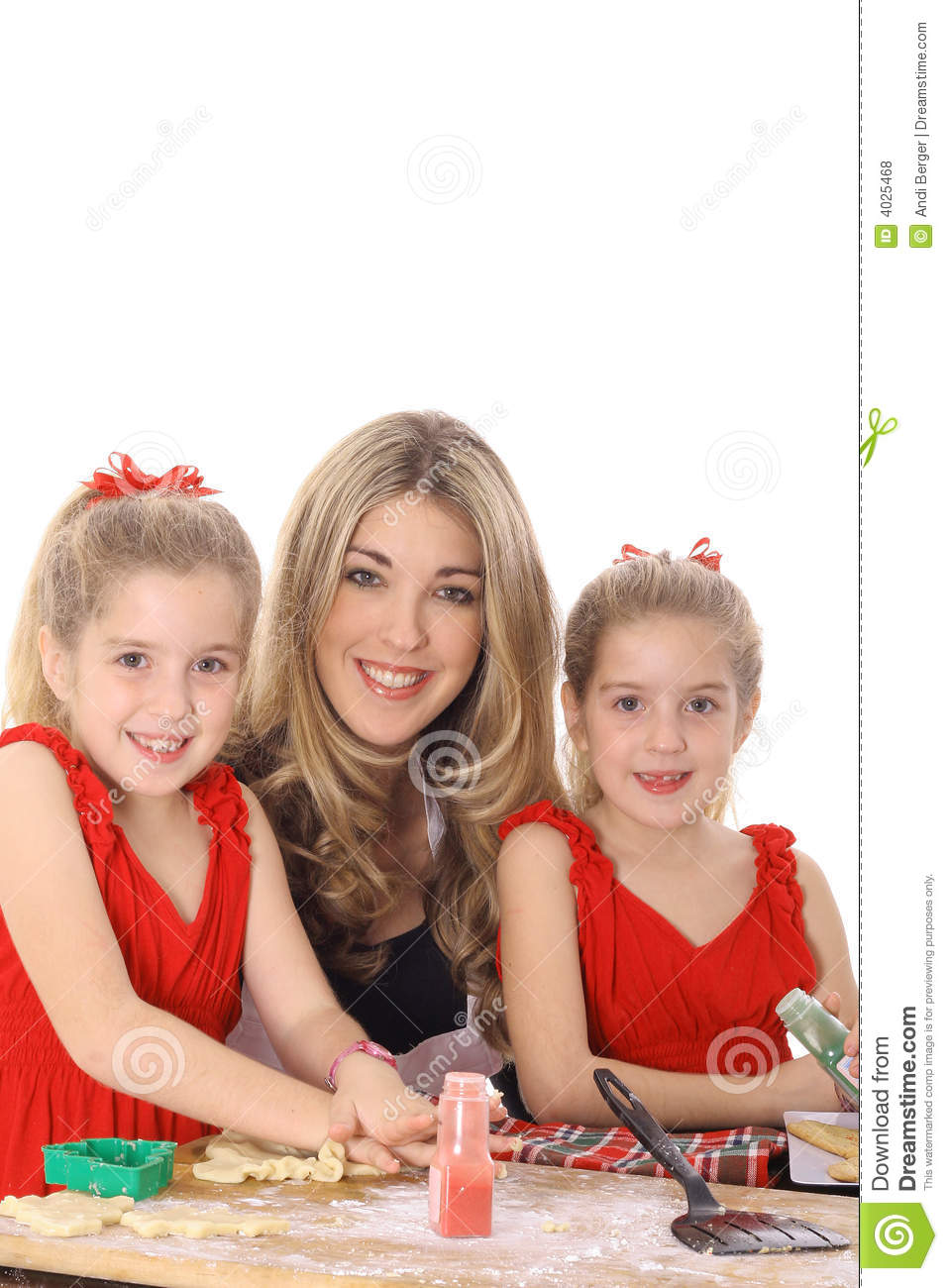 Happy mom with twin daughters decorating cookies