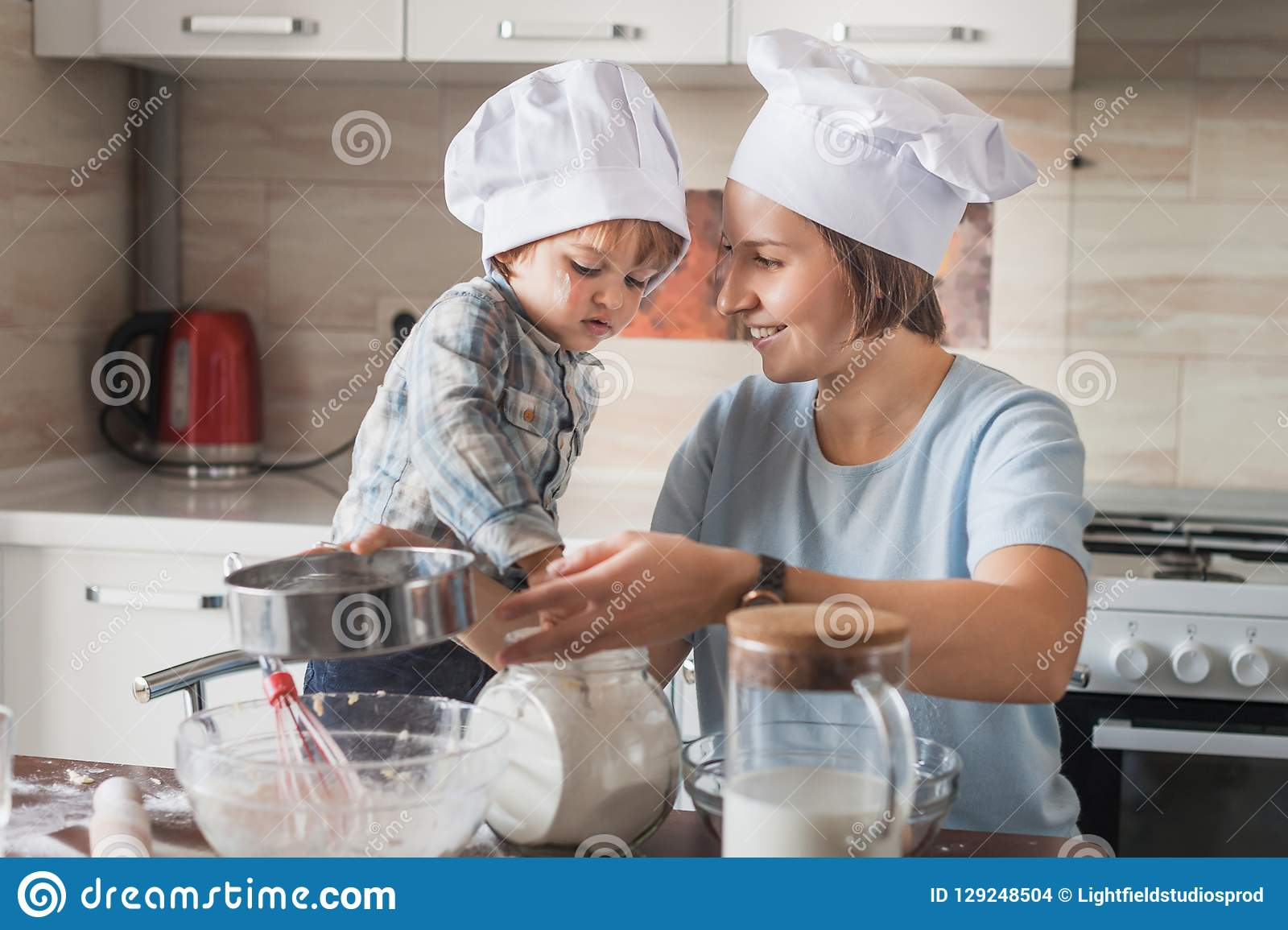 happy mother and adorable child in chef hats preparing dough on messy table
