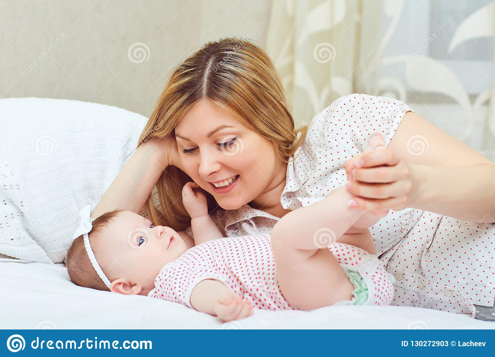 A happy mother with a baby plays on a bed.