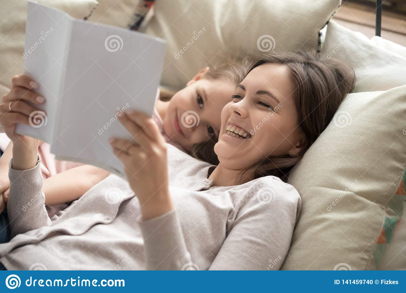 Happy mother and child daughter reading book laughing in bed