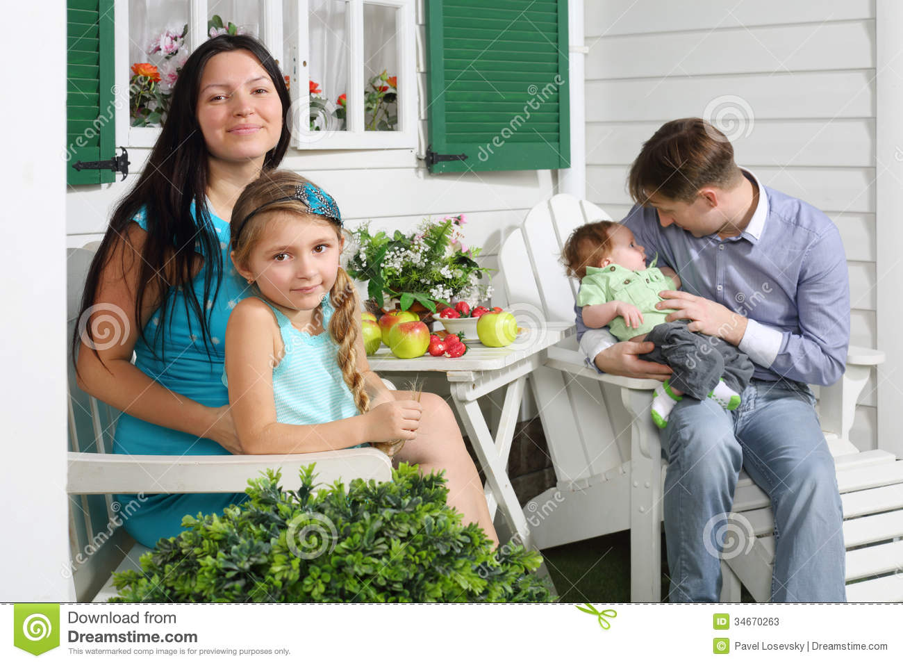 Happy Mother With Daughter And Father With Son Sit At