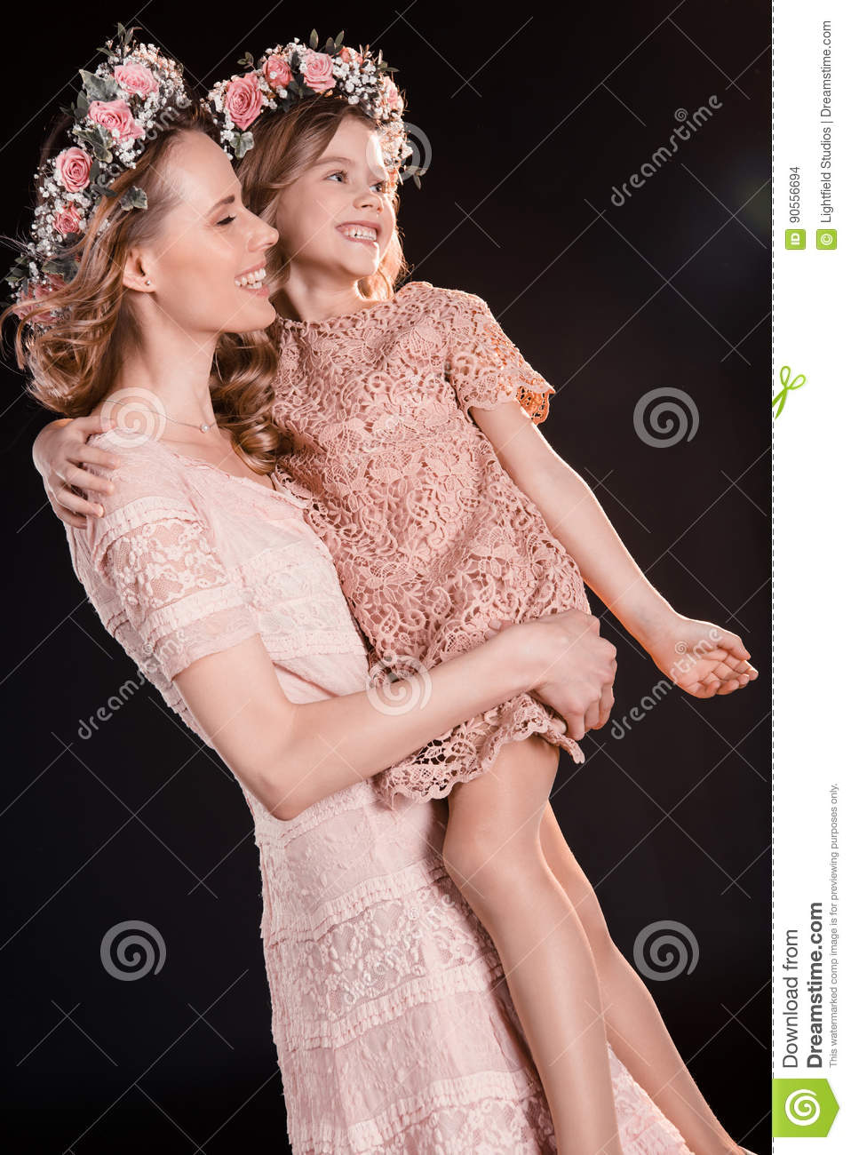 7cfce2436a Beautiful happy mother and daughter in floral wreaths and pink dresses