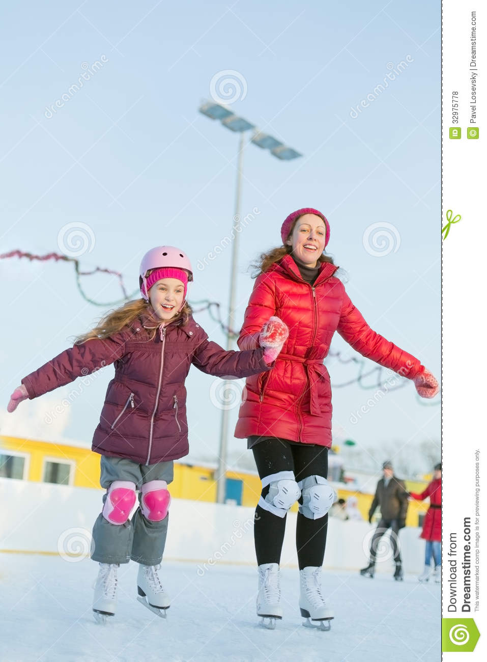 Happy mother and daughter are skating at outdoor skating rink