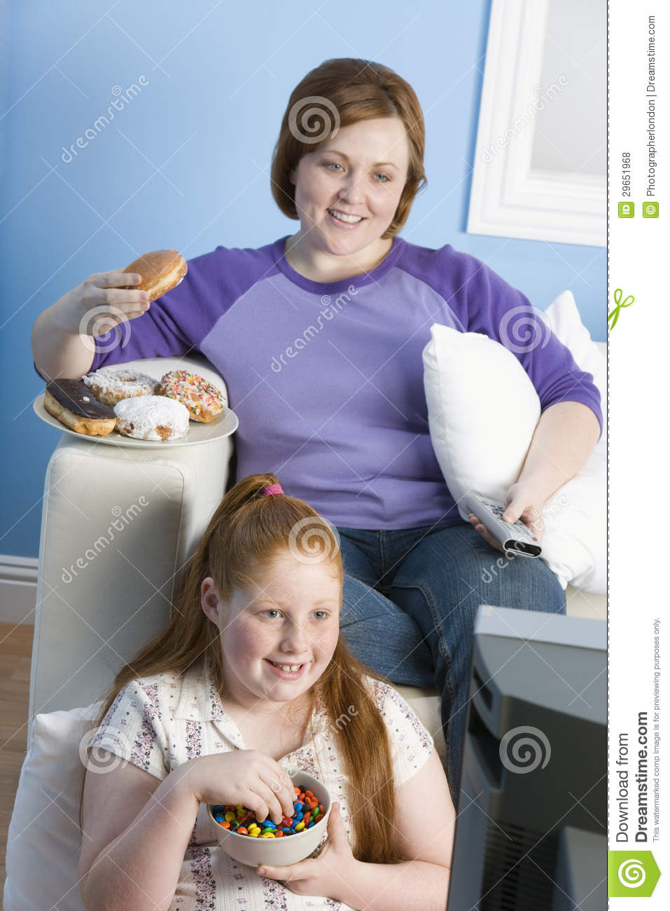 Watch Mom In Bedroom Camera: Couch Potato Eating And Watching TV Stock Image