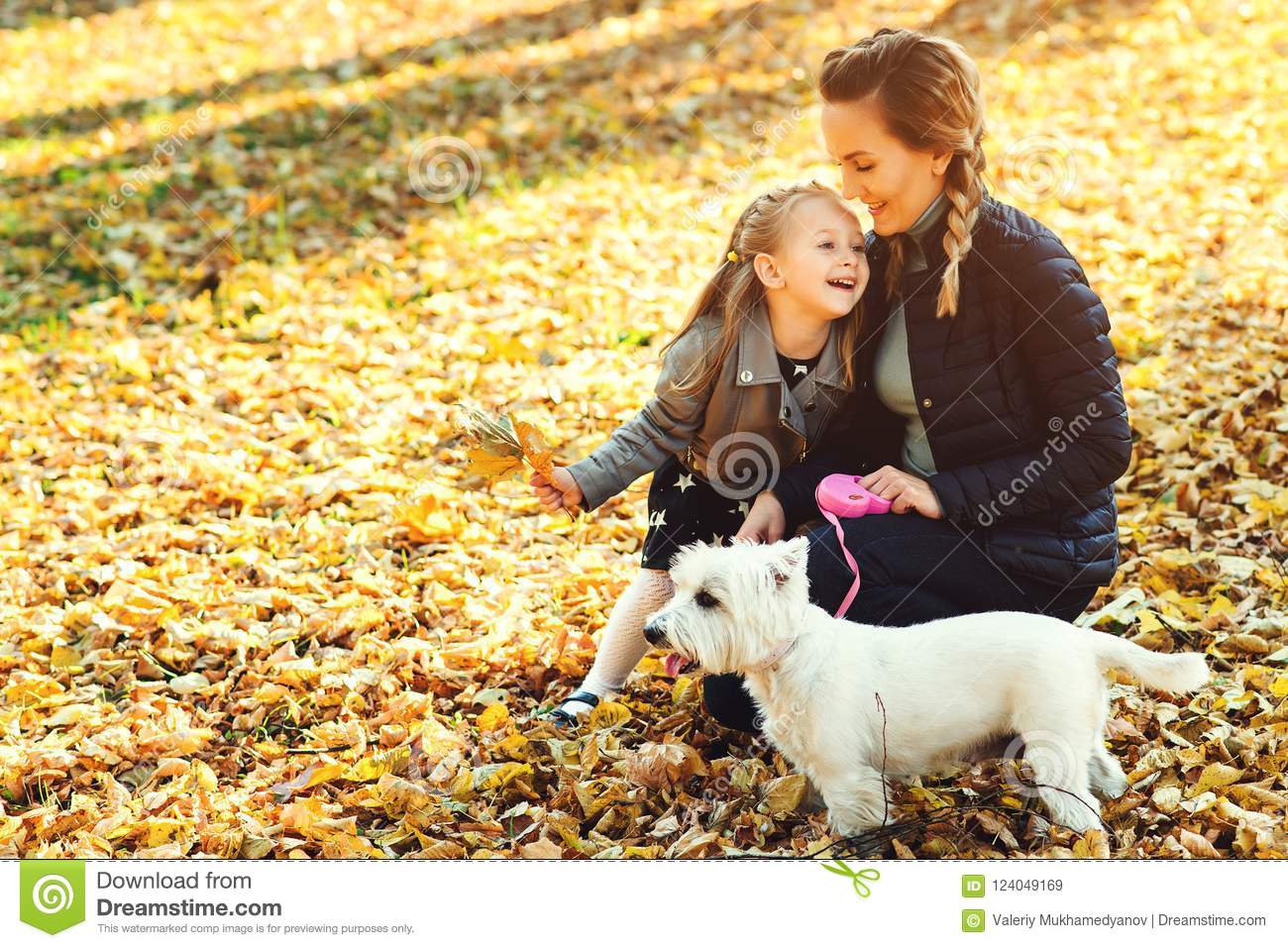Happy mother and her daughter playing with dog in autumn park. Family, pet, domestic animal and lifestyle concept. Autumn time. Ha
