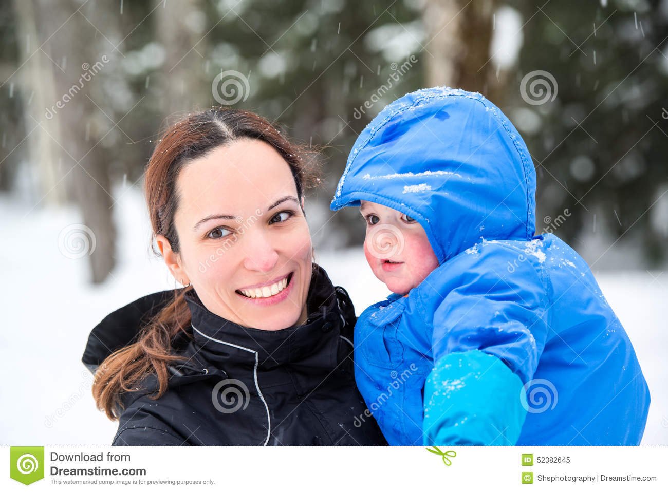 Happy Mother Holding Baby Son Outside in the Winter