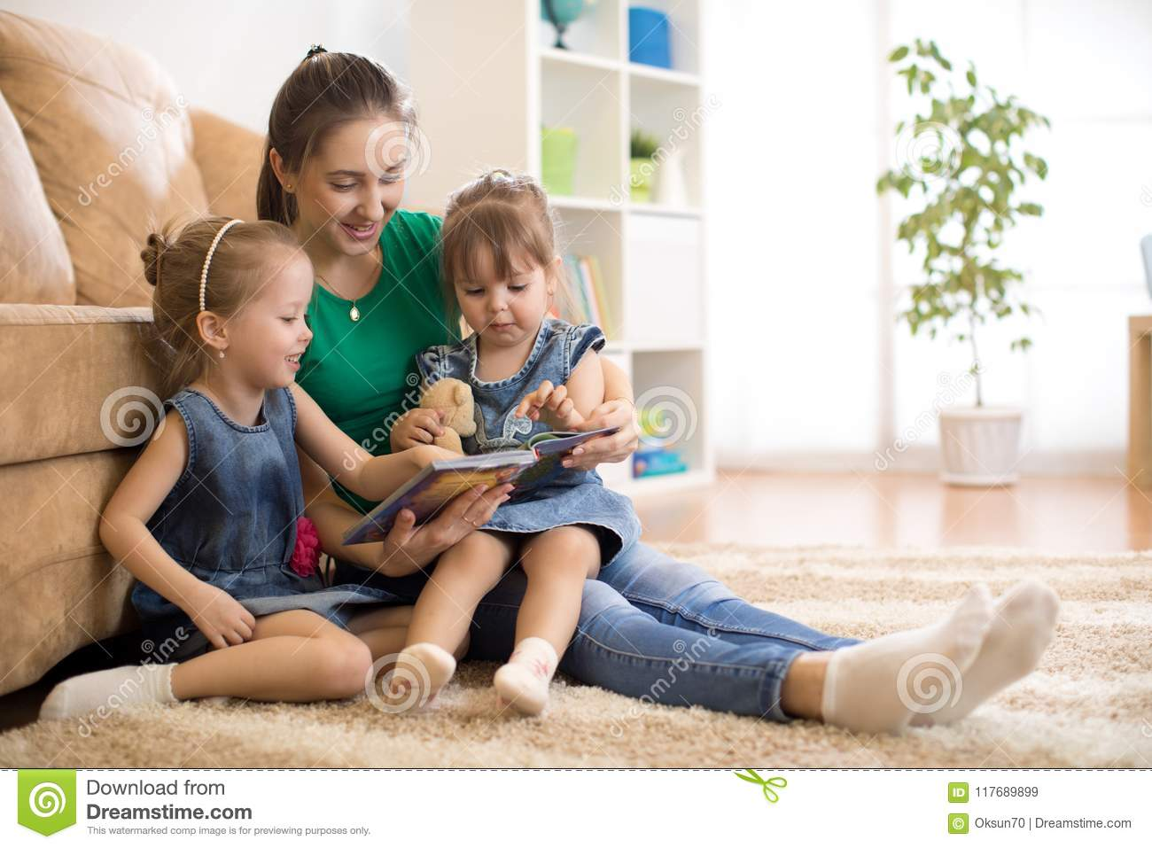 Happy mother and little daughters reading a book together in the living room at home. Family activity concept.