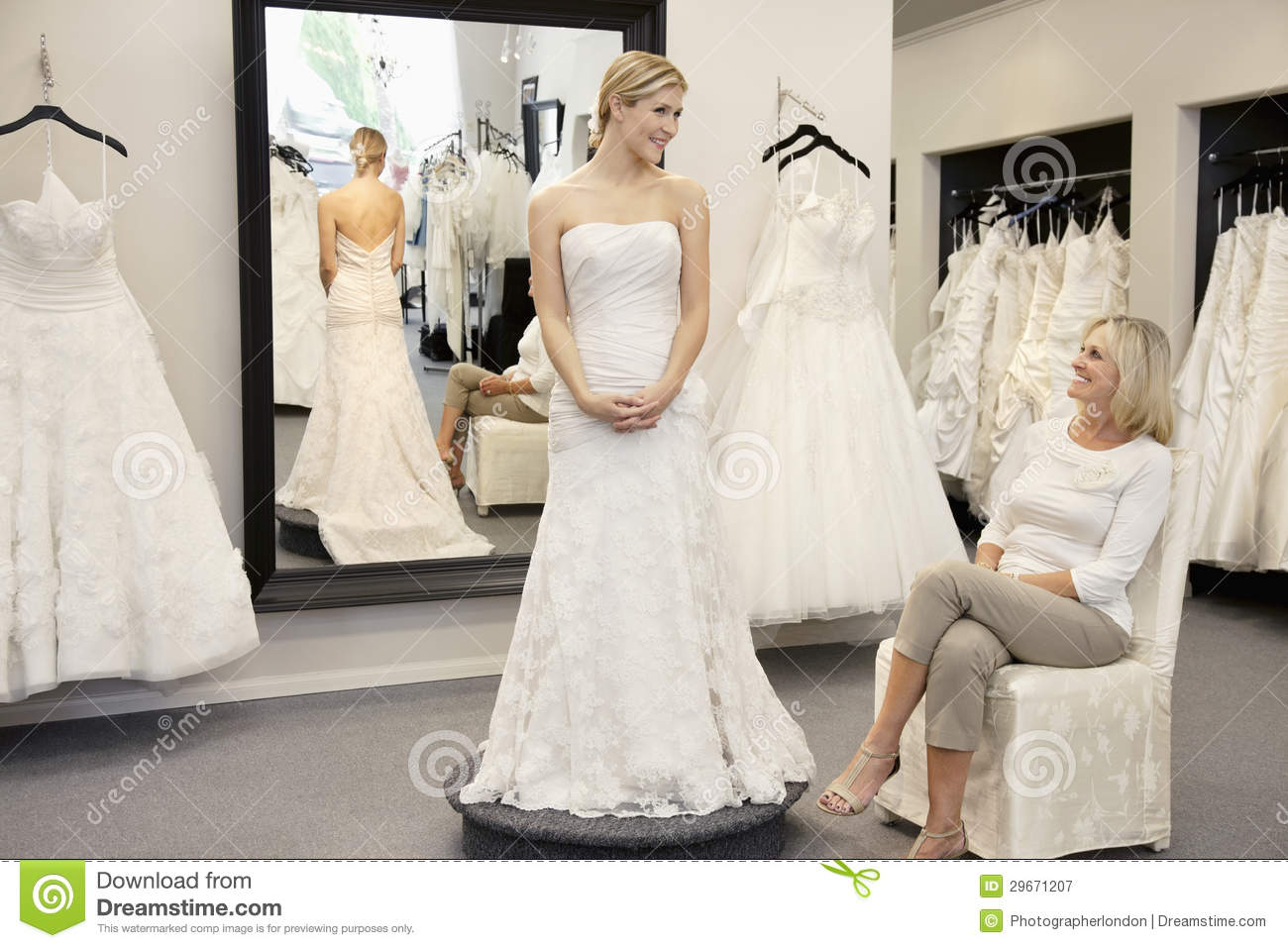 Happy Mother Looking At Young Daughter Dressed In Wedding