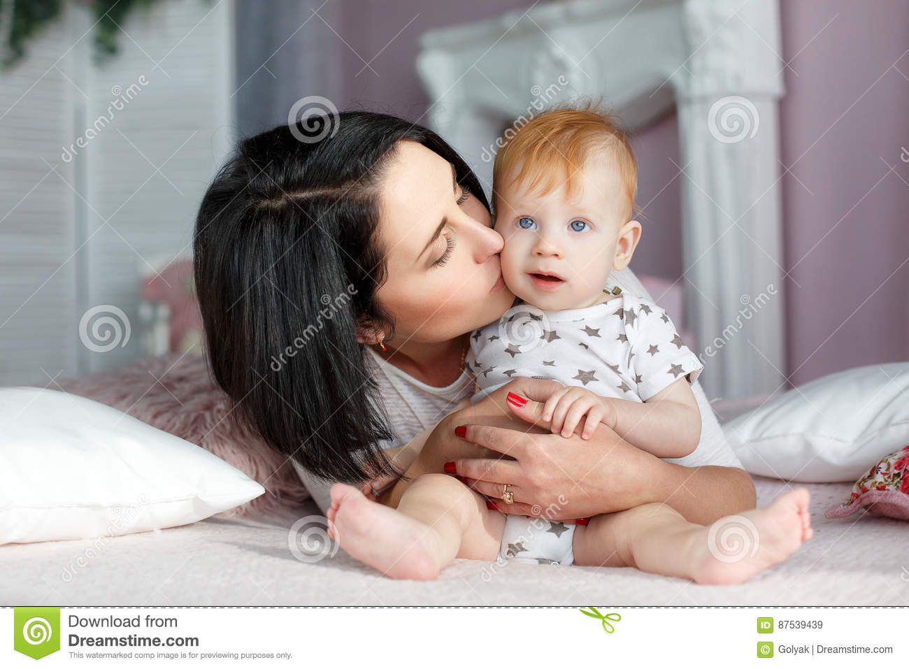 Happy Mother Playing With Baby Boy Lying On Bed At Home Stock Image