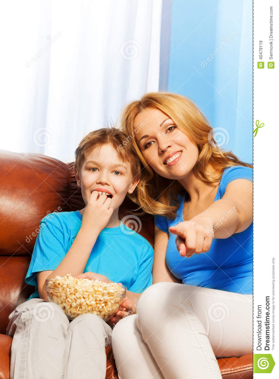 Watch Mom In Bedroom Camera: Happy Mother Pointing Forward And Son Watch TV Stock Photo