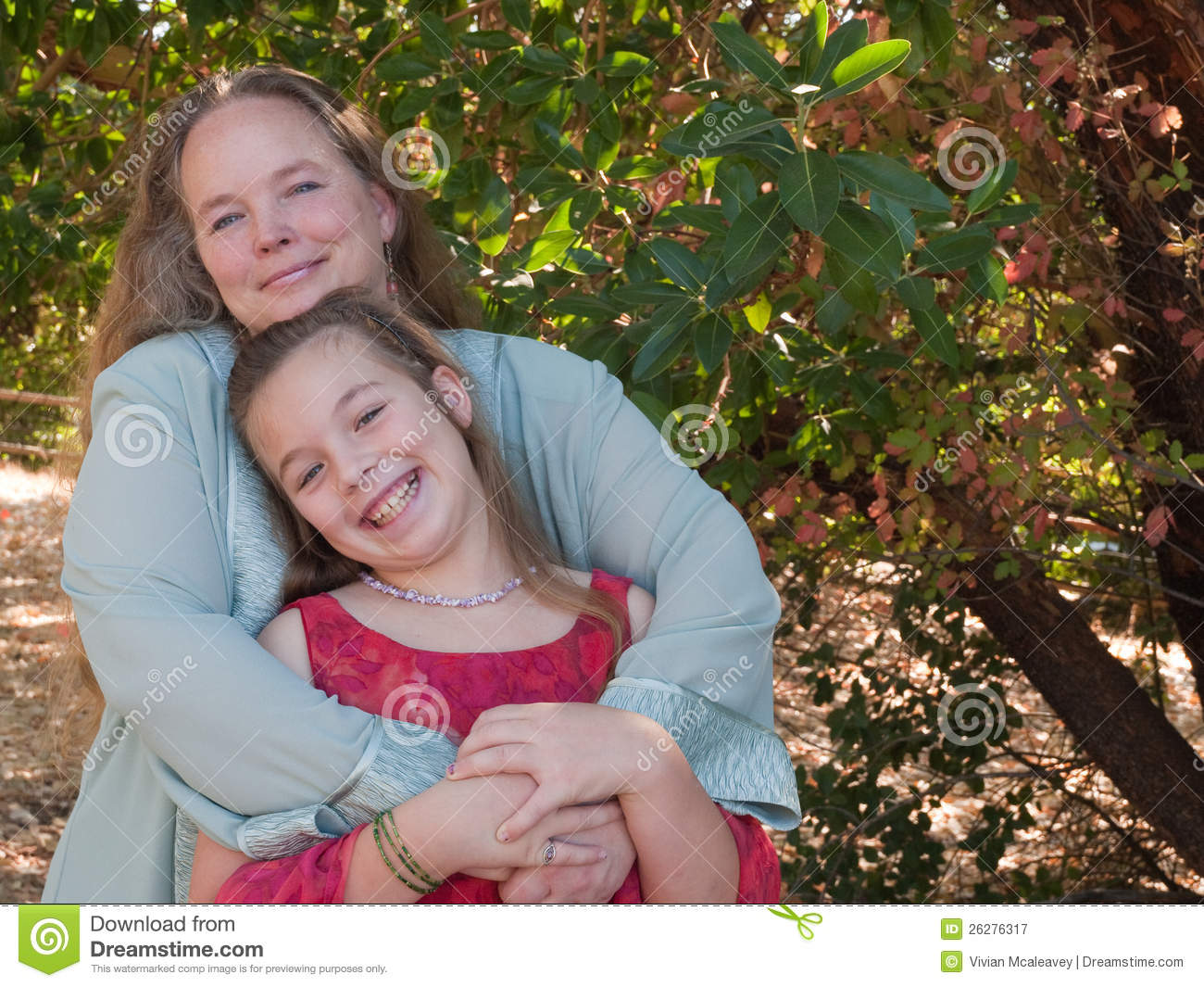 Happy mother and pre-teen daughter standing together outside under a ...