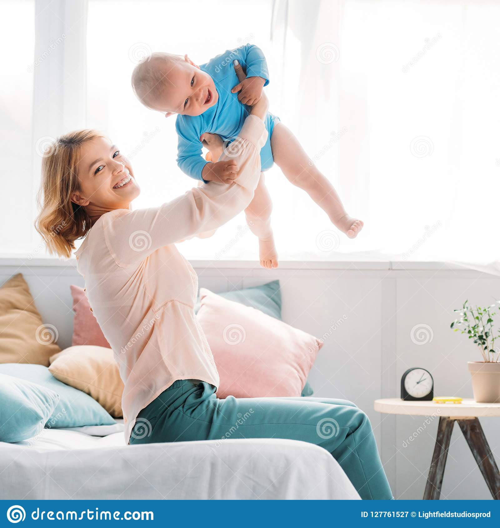 happy mother raising up laughing little child