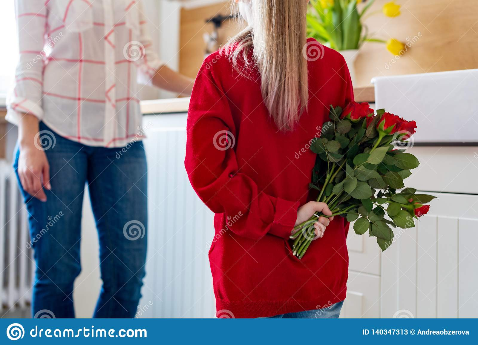 Happy Mother`s Day or Birthday Background. Adorable young girl surprising her mom with bouquet of red roses. Family celebration.