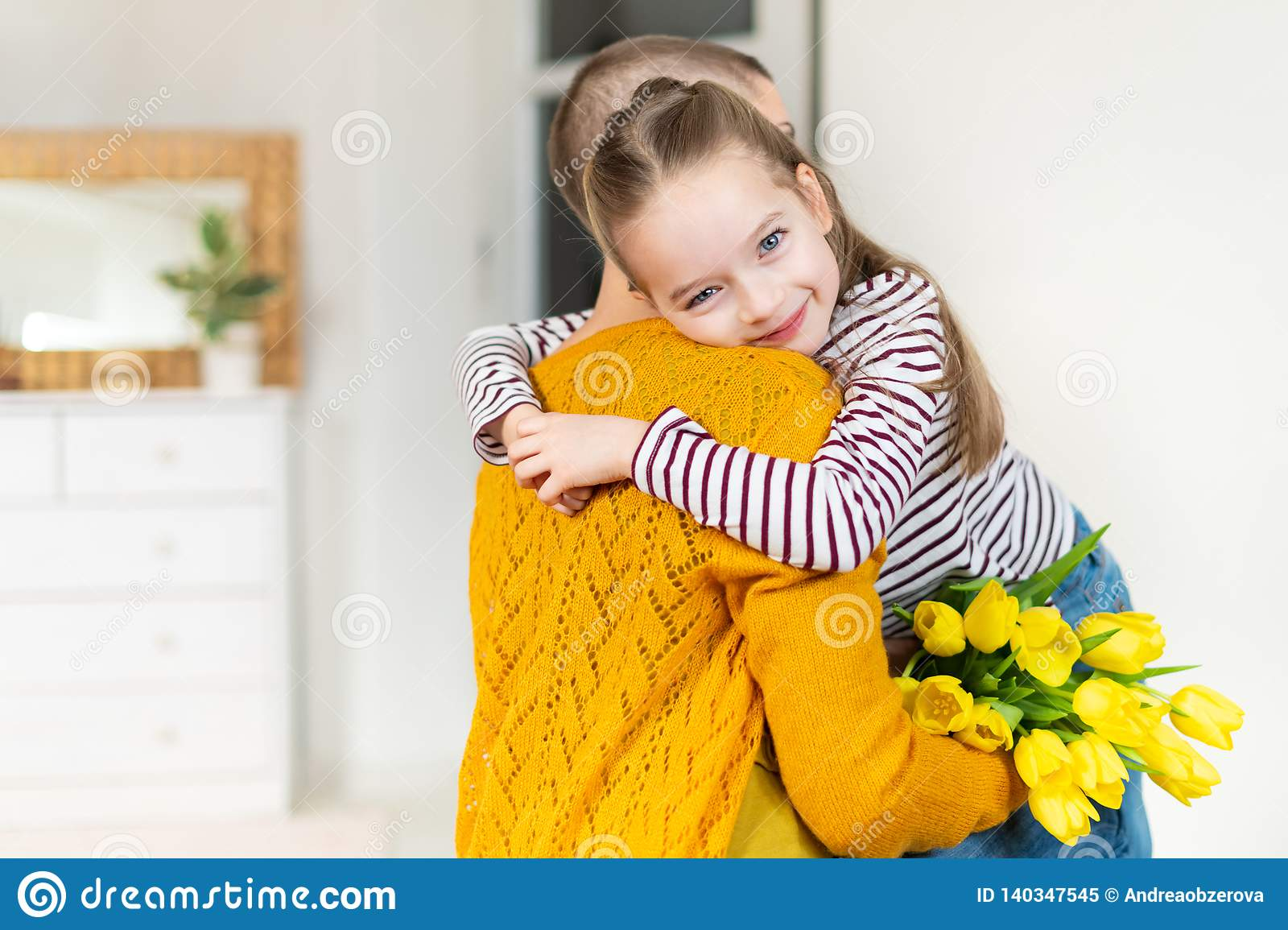 Happy Mother`s Day or Birthday Background. Adorable young girl surprising her mom, young cancer patient, with bouquet of tulips.