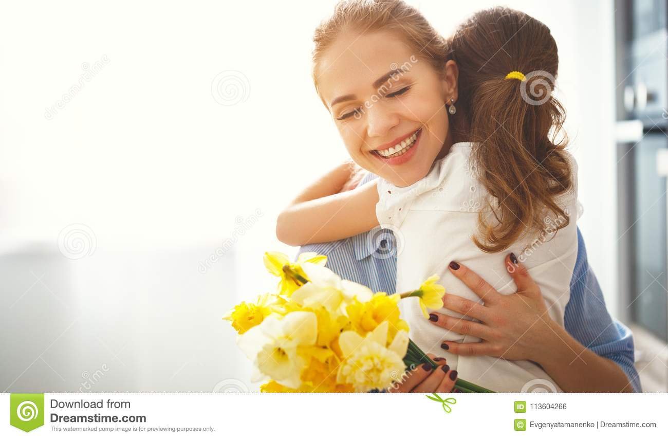Happy mother`s day! child daughter gives mother a bouquet of f