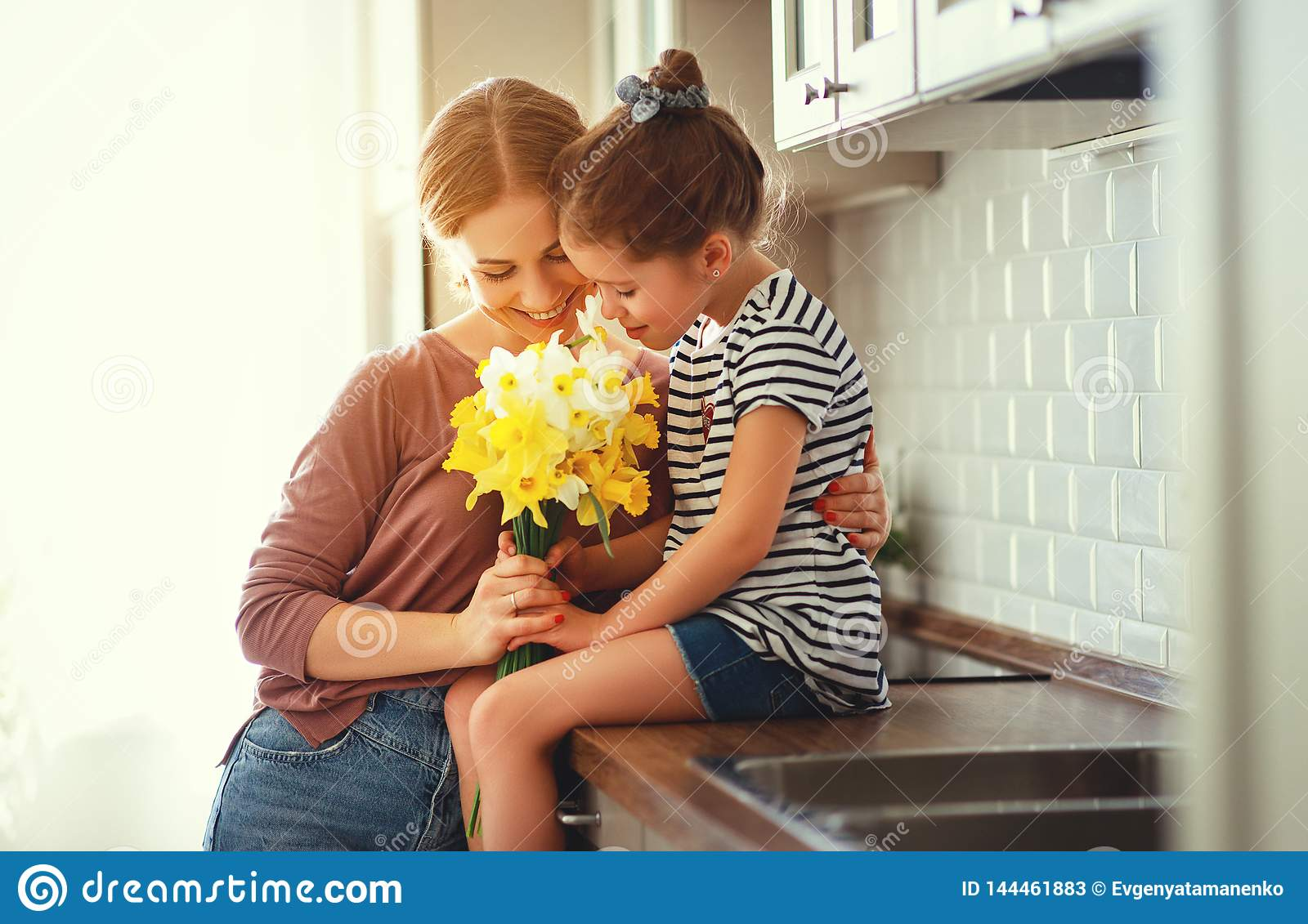 Happy mother`s day! child daughter   gives mother a bouquet of flowers to narcissus and gift