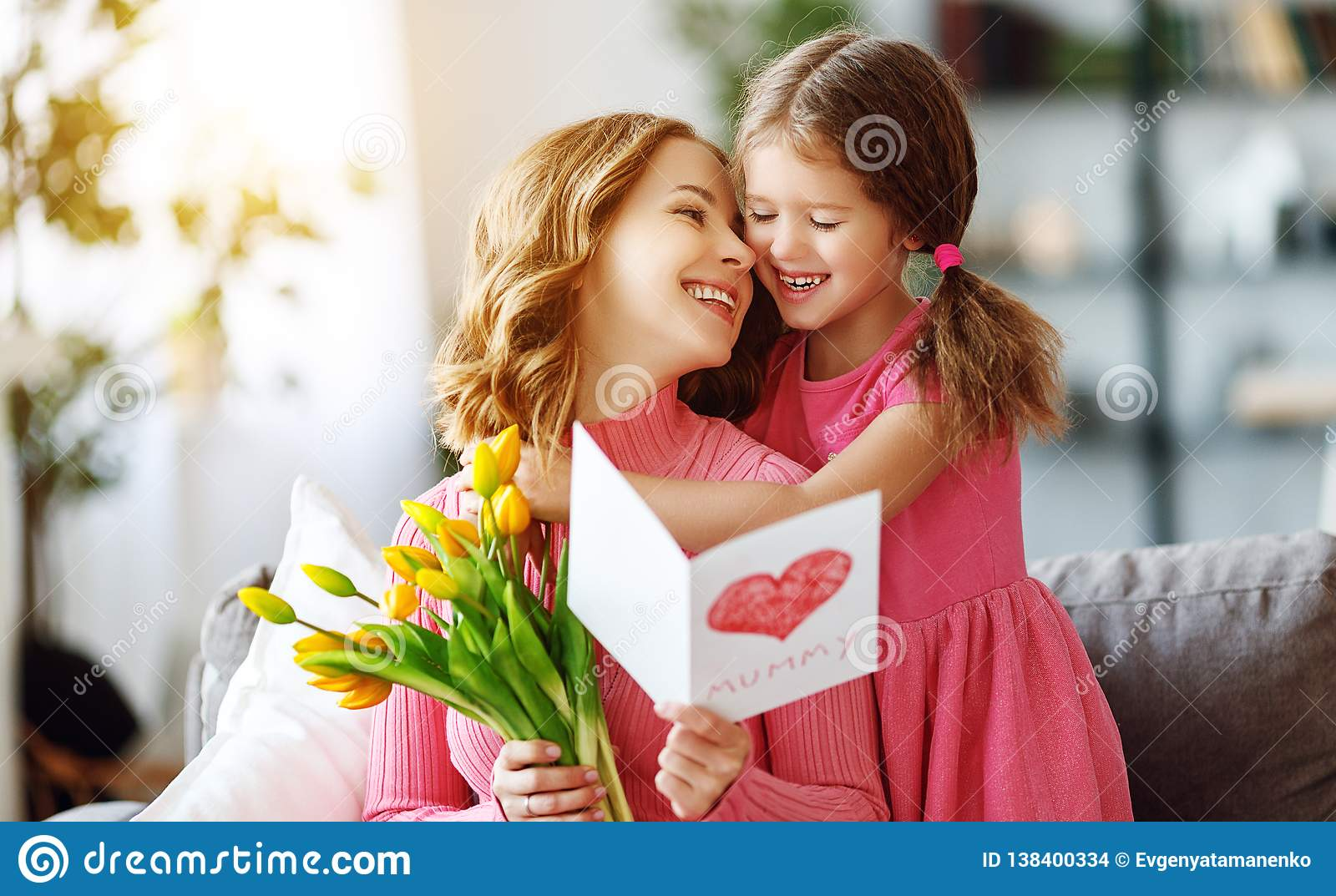 Happy mother`s day! child daughter gives mother a bouquet of flowers to tulips and postcard