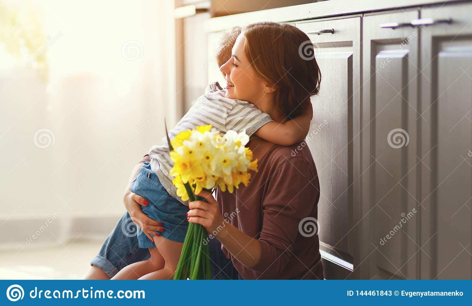 Happy mother`s day! child son gives flowersfor  mother on holiday