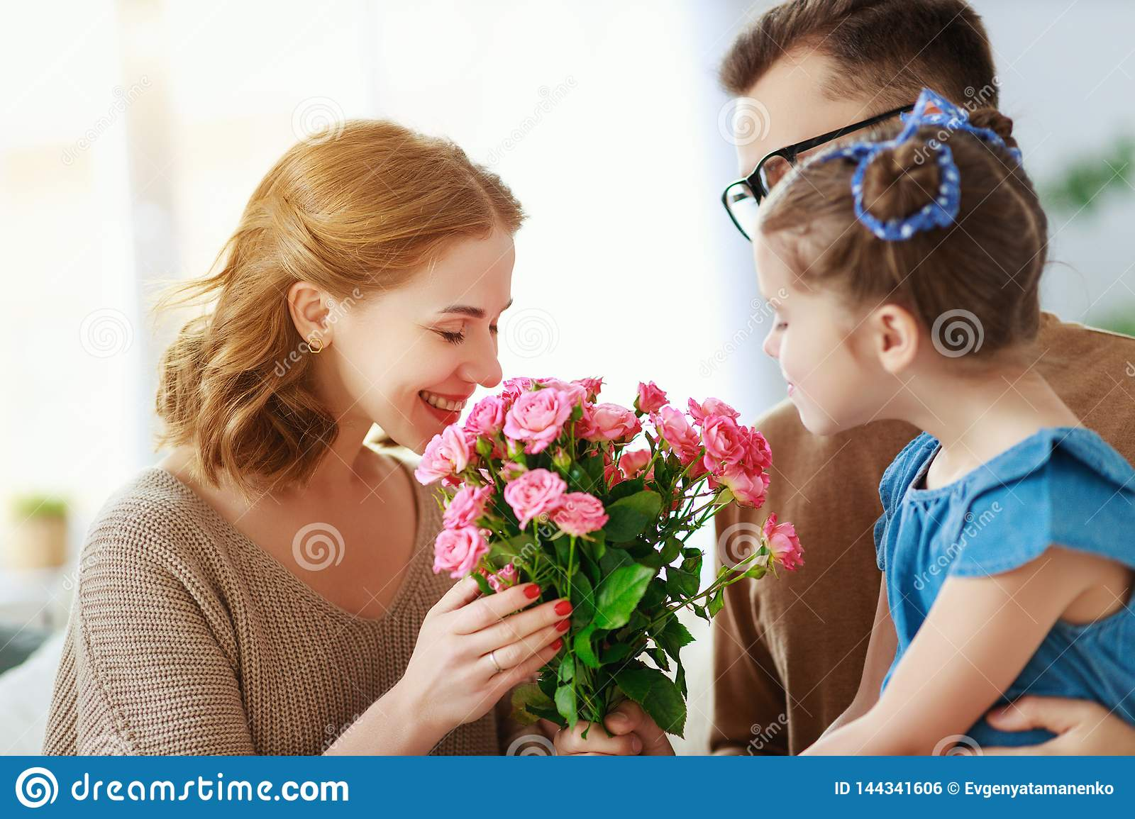 Happy mother`s day! father and child congratulate mother on holiday