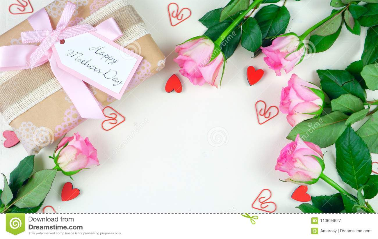Mother`s Day overhead with gift and pink roses on white wood table background