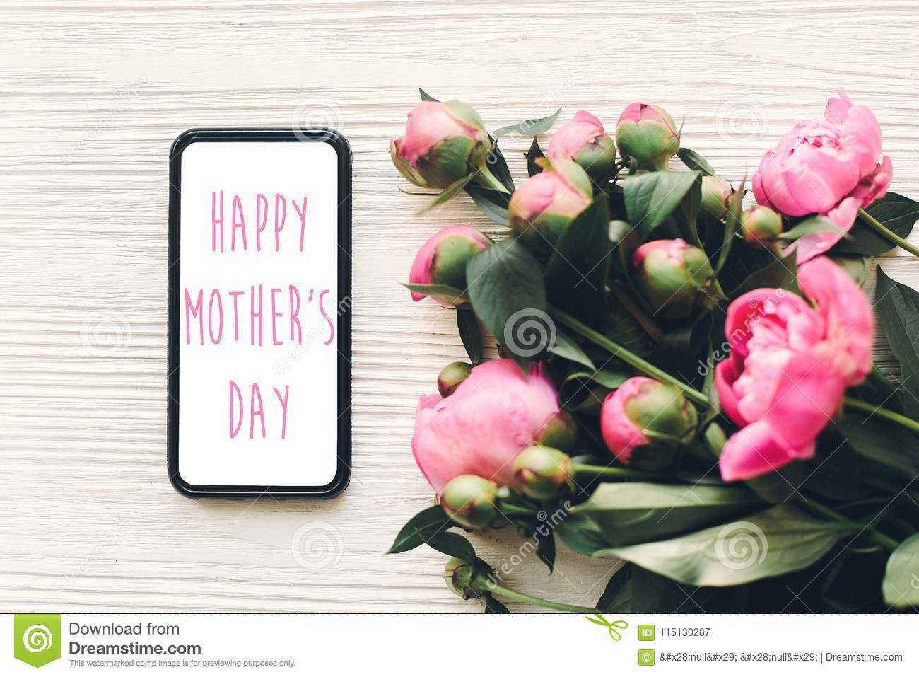 Happy Mothers Day Text On Phone Screen And Pink Peonies On Rust
