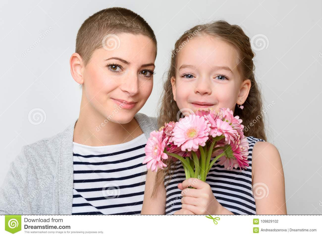 Happy Mother`s Day, Women`s day or Birthday background. Cute little girl giving mom, cancer survivor, bouquet of pink daisies.