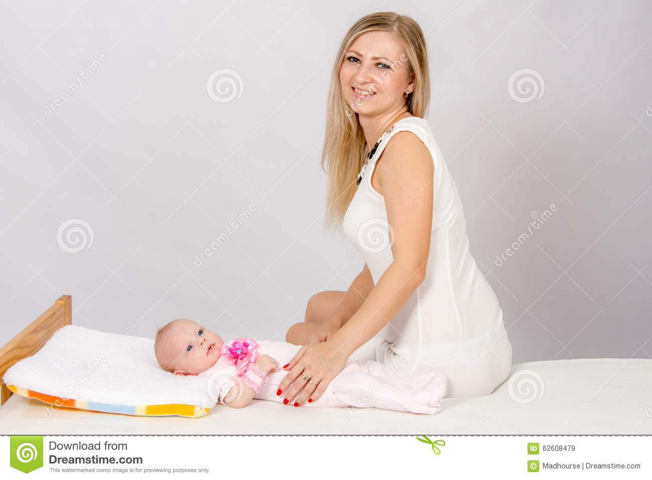 Happy mother sitting on a bed at his two-month daughter and looks in the picture