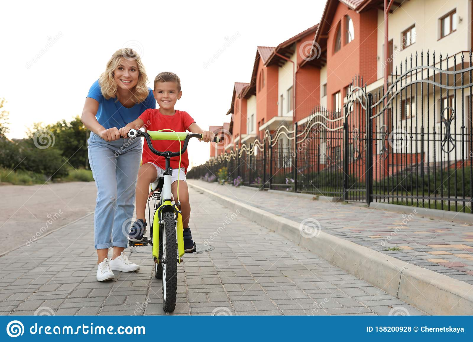 Happy mother teaching her son to bicycle in city