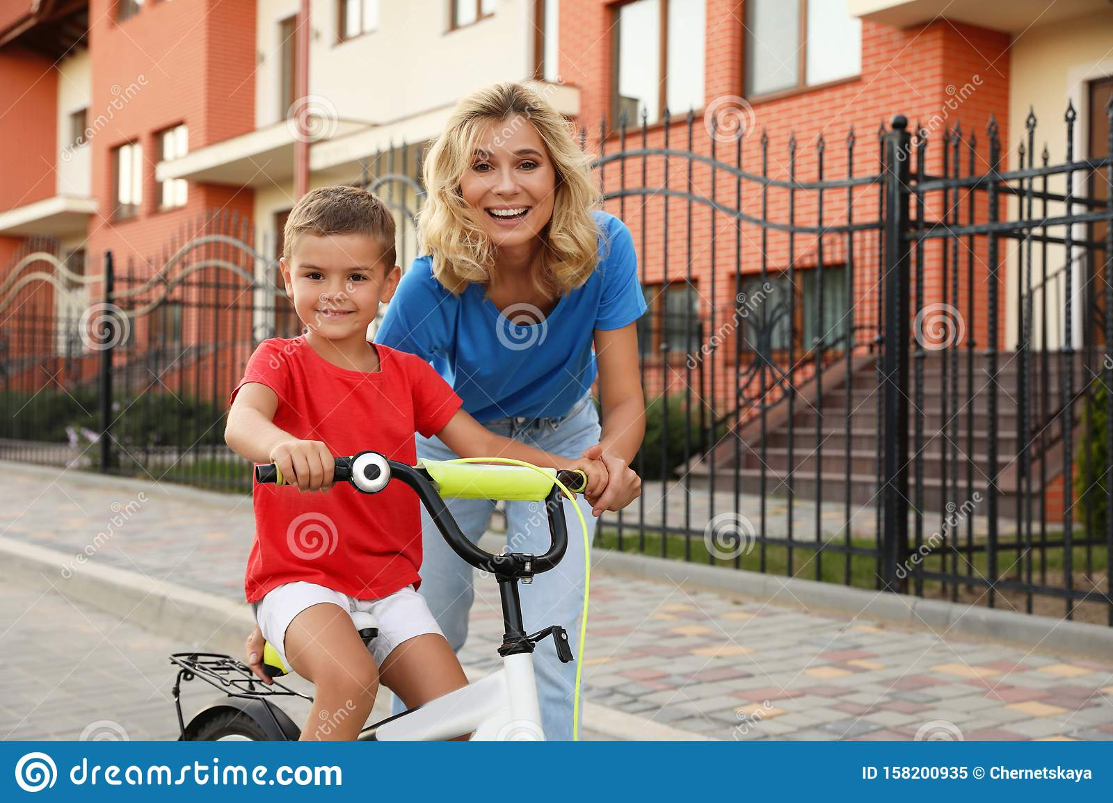 Happy mother teaching her son to ride bicycle