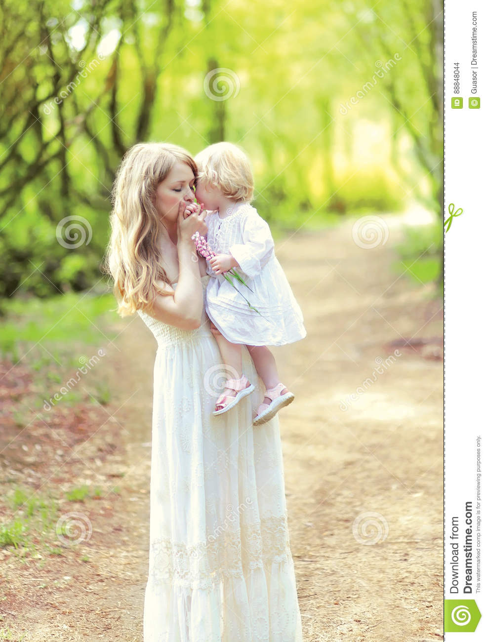 Happy mother tenderly kissing her baby holding on hands in spring