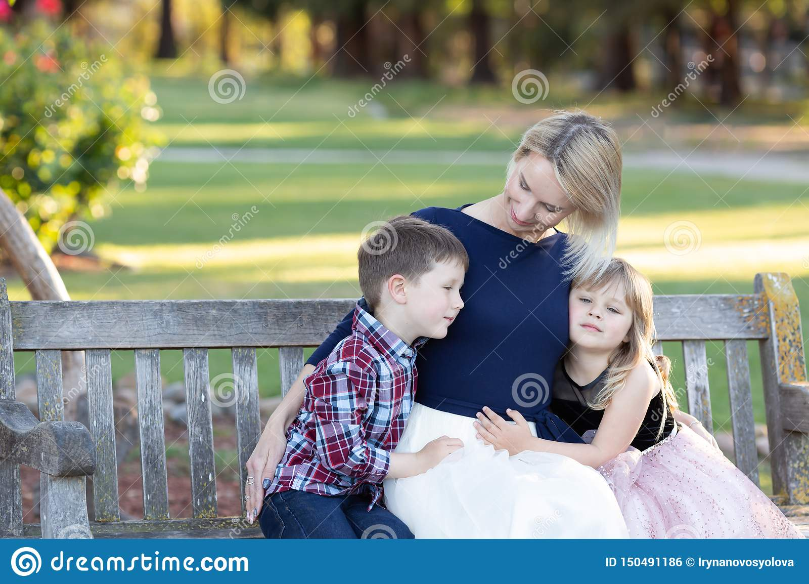 Happy mother with two children sitting on a wooden bench in a garden