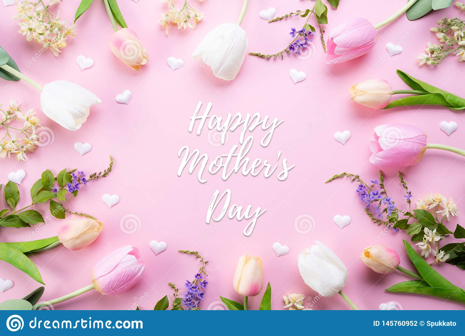 Happy mothers day concept. Top view of pink tulip flowers in frame with happy mother`s day text on pink pastel background. Flat