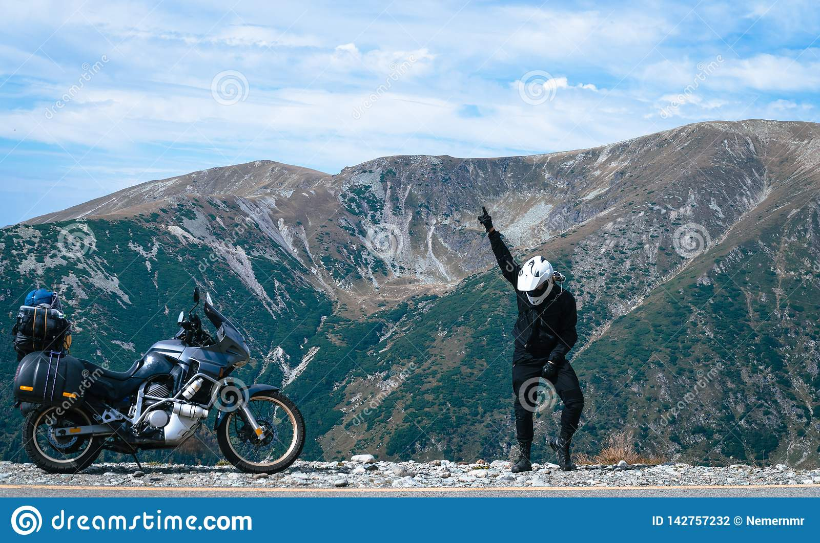 Happy motorcyclist man is dancing and Adventure Motorbike on the top of the mountain. Motorcycle trip. World Traveling, Lifestyle
