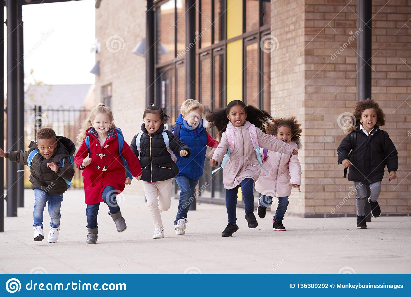 A happy multi-ethnic group of young school kids wearing coats and carrying schoolbags running in a walkway with their classmates o