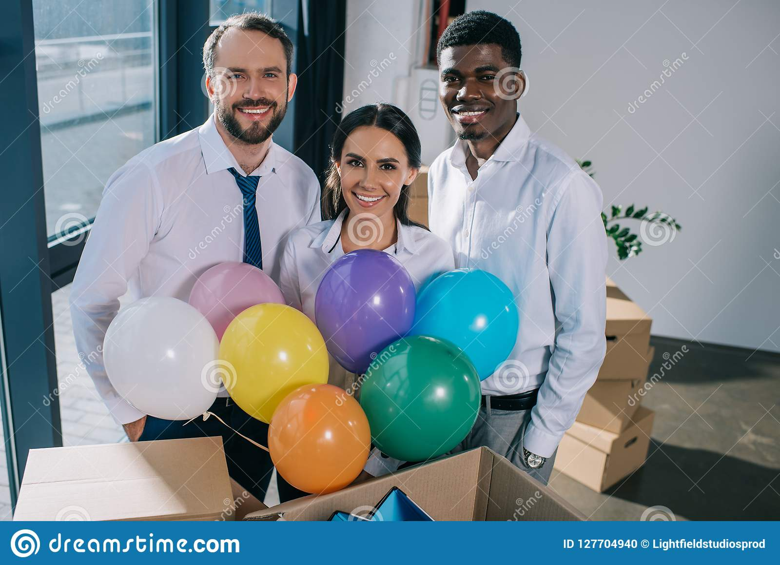 happy multiethnic coworkers holding colorful balloons and smiling at camera in new