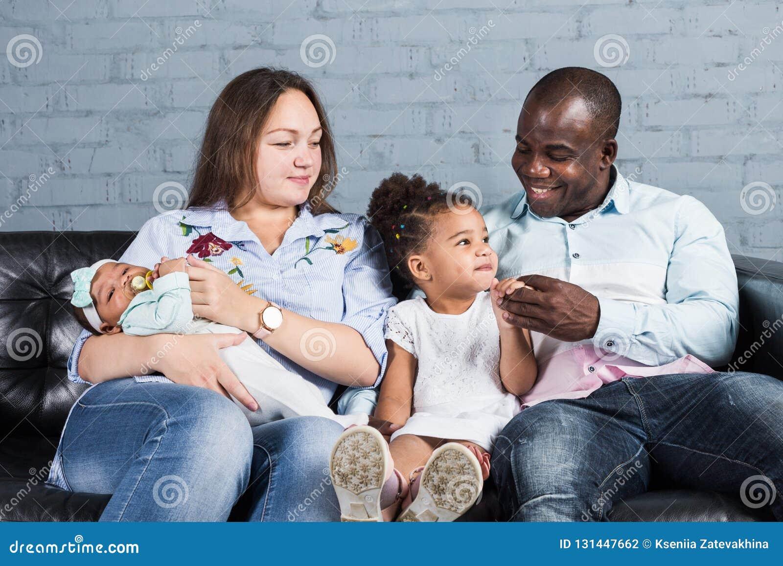 Happy multiethnic family sitting on the sofa in modern interior
