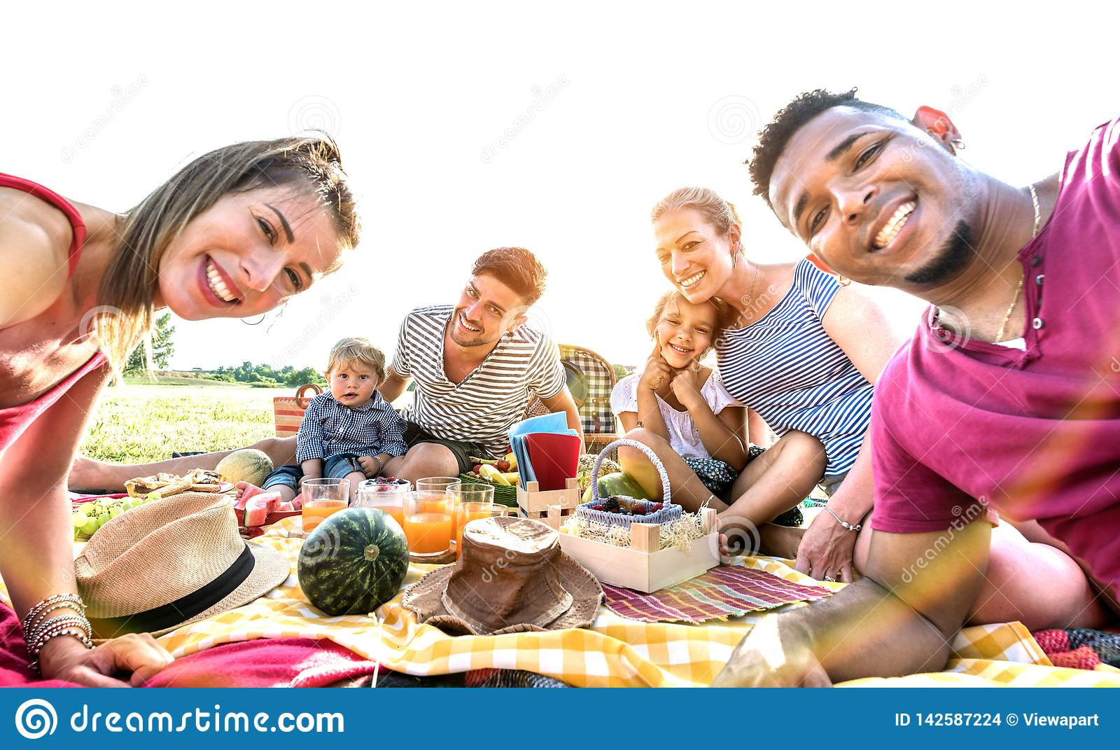 Happy multiracial families taking selfie at pic nic garden party - Multicultural joy and love concept with mixed race people