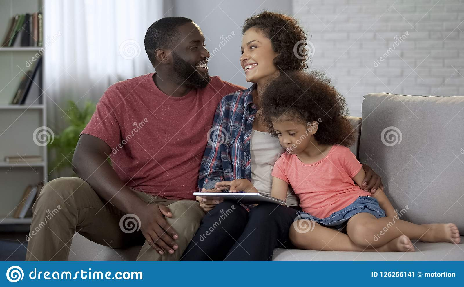 Happy multiracial family planning trip for holidays, booking online on tablet