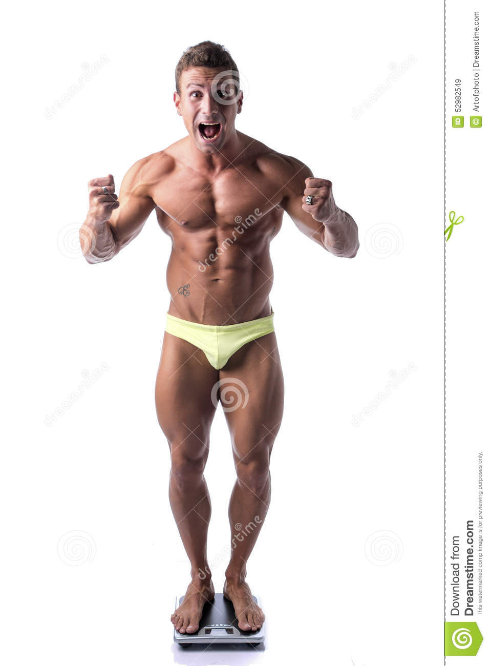 Happy muscular young man weighing himself on scale